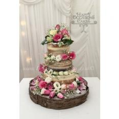 Three tier naked wedding cake with fresh flowers...